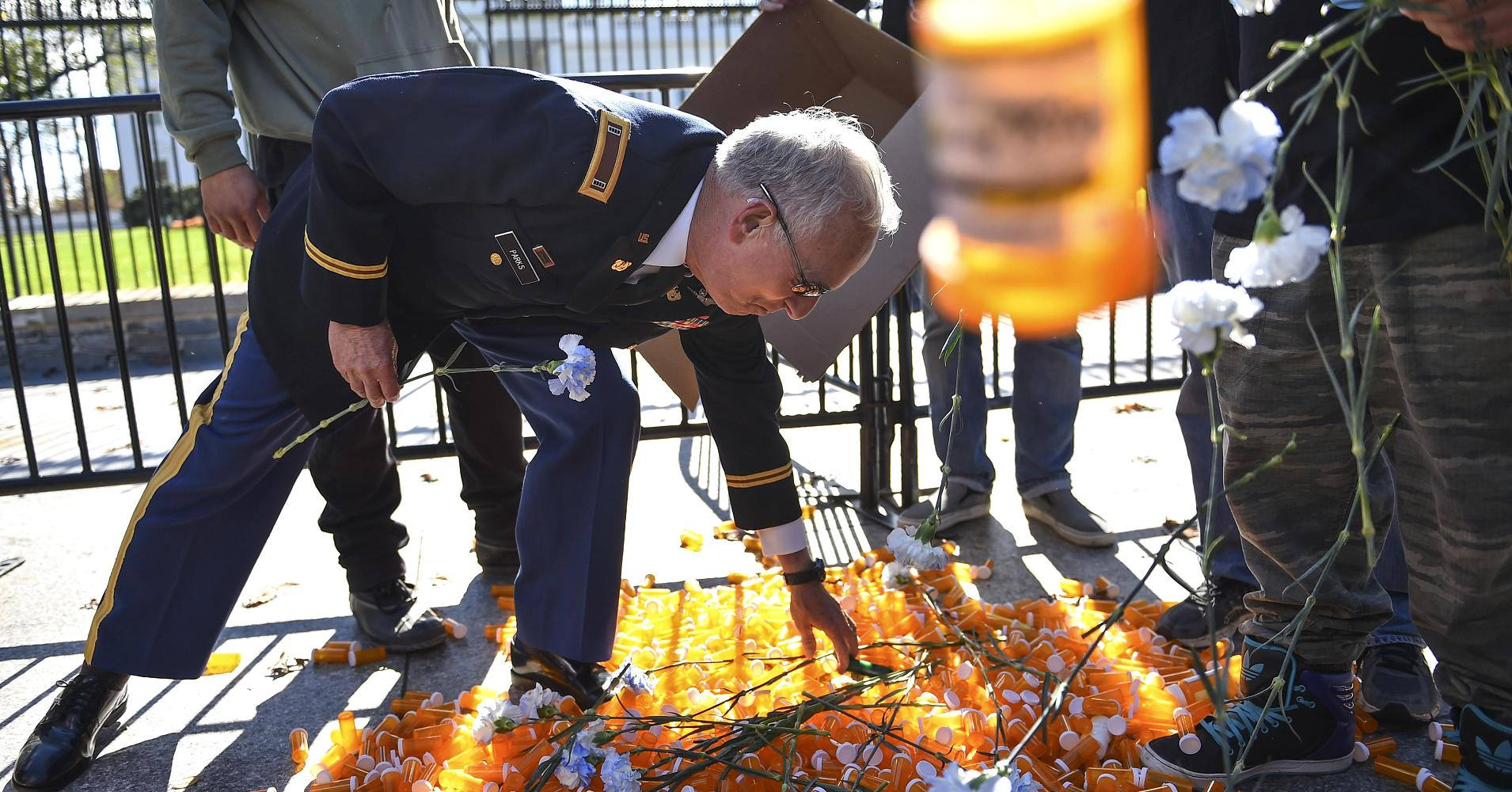 Army veteran CW4 Perry Parks reaches to lift a symbolic pill bottle that was placed in front of the White House by a group of medical marijuana supporters to raise awareness of opioid addiction.