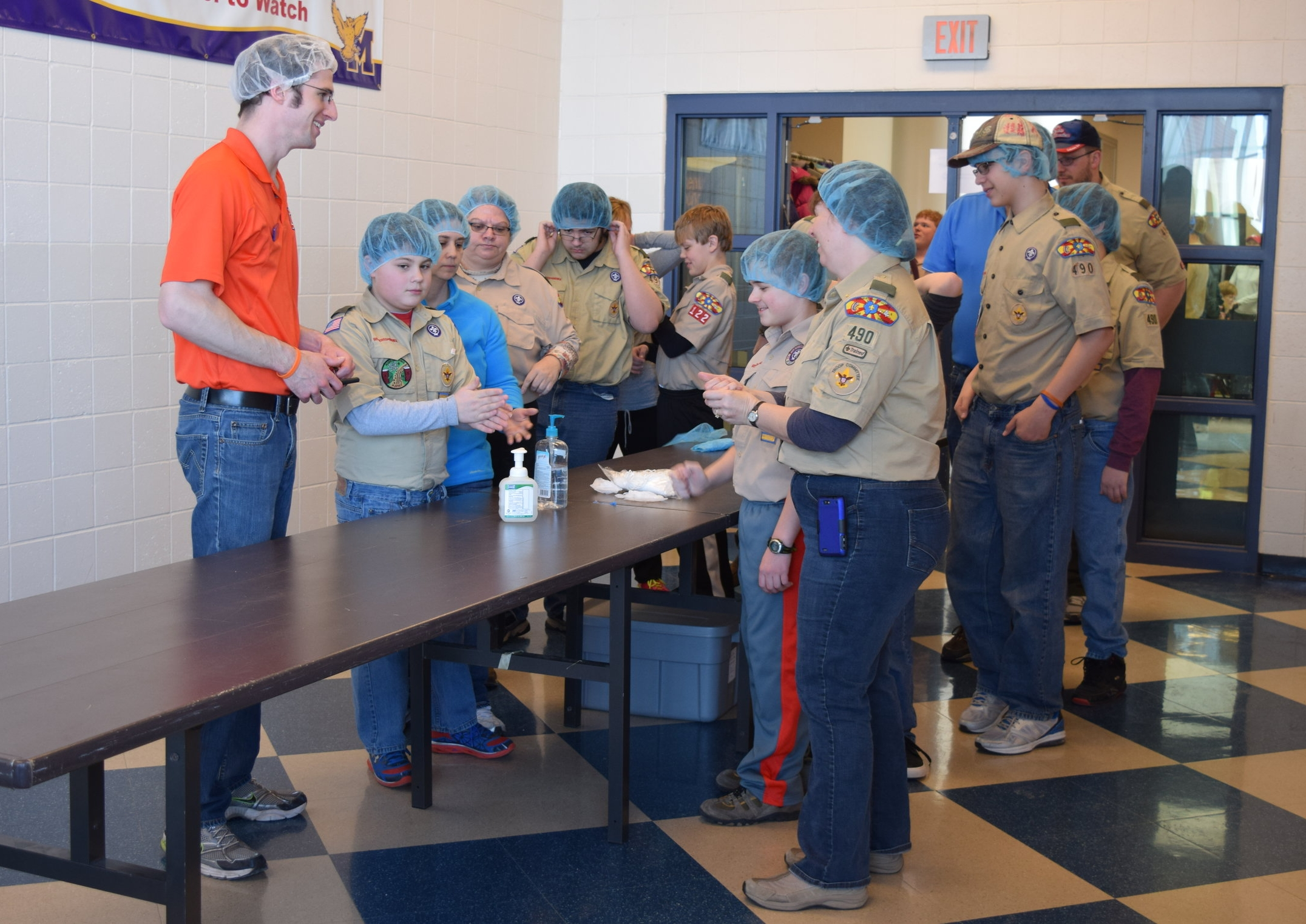 A student leader from Illini Fighting Hunger leads a boy scout troop as they prepare to package meals in Monticello, IL.