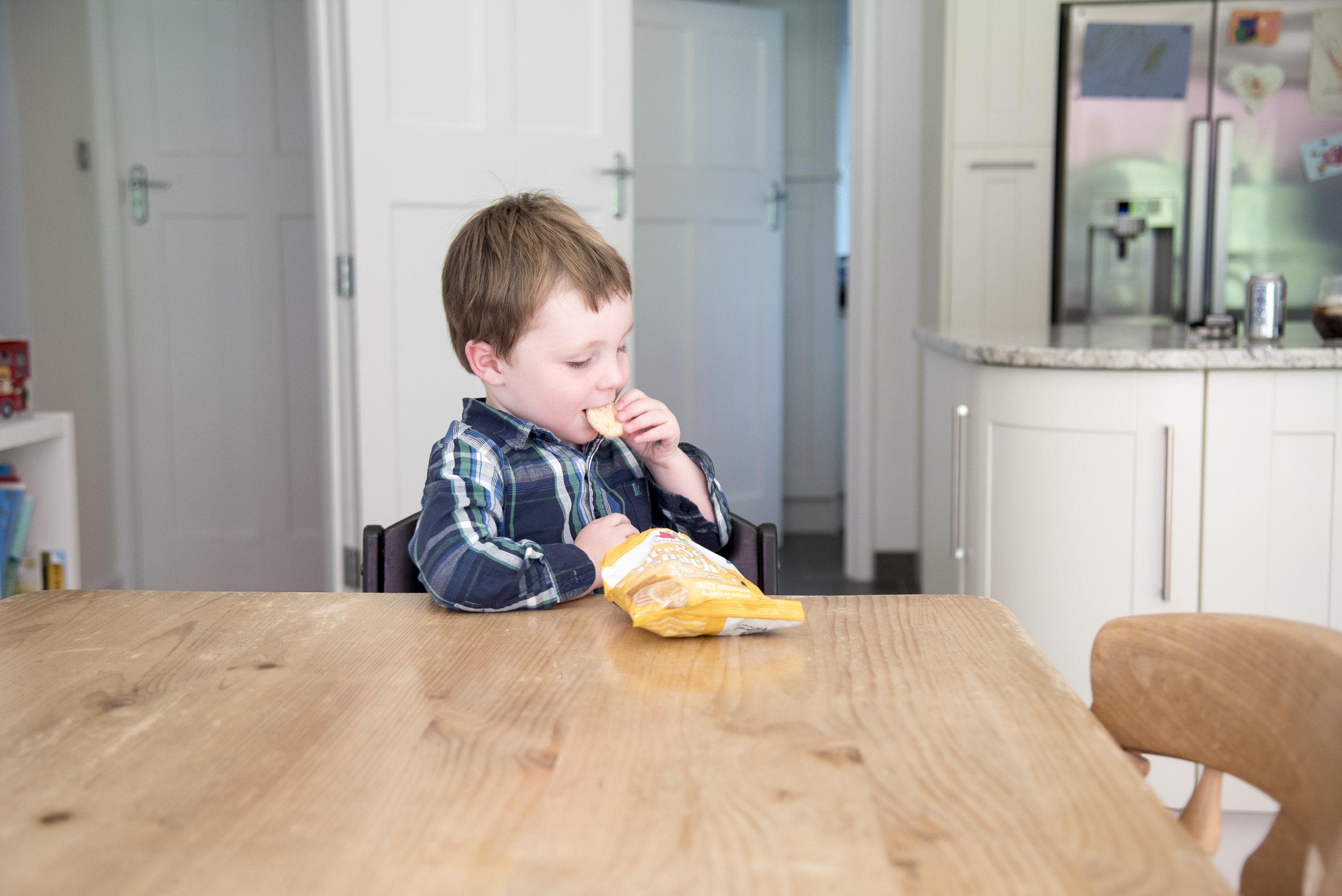 sally-hornung-photography-boy-eating-crisps-table.jpg