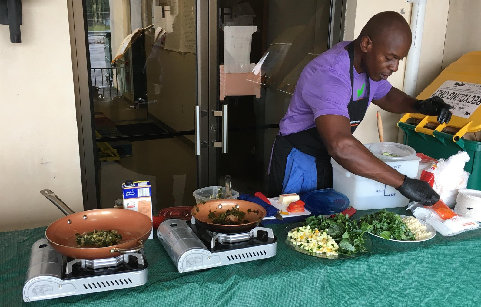 Volunteer Marvin cooks up a delicious sample at the Franklin Co. Produce Stand featuring fresh kale and collard greens!