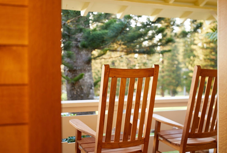 View from Lanai Room porch with two wooden rocking chairs facing balcony and tall pine trees