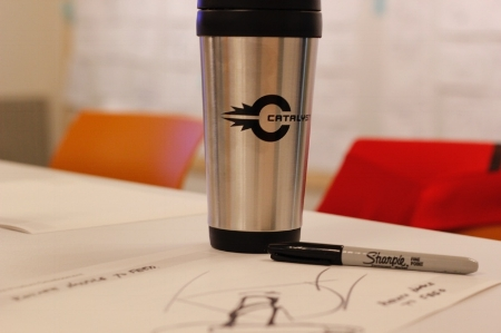 Catalyst mug on top of whiteboard product design sketches