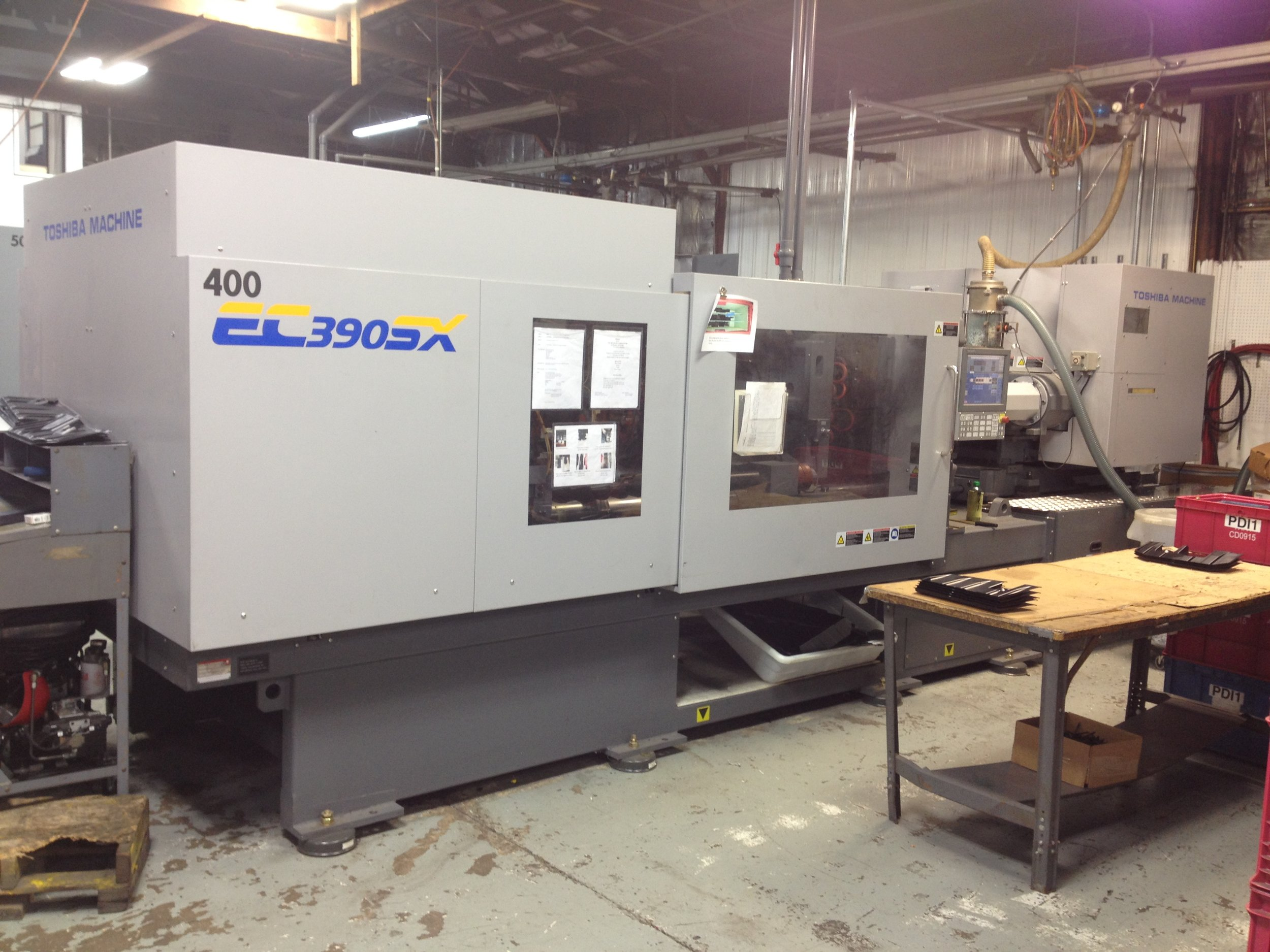 "Toshiba EC390SX 400T  Equipped with a robot 385 Ton Max Part Length/Width 25"" x 24"" Max Part Weight: 37 oz Max Mold Width: 31.9″ Min Stack Height: 11.8 Max Daylight: 55.9″ Ejector Stroke: 5.9″"