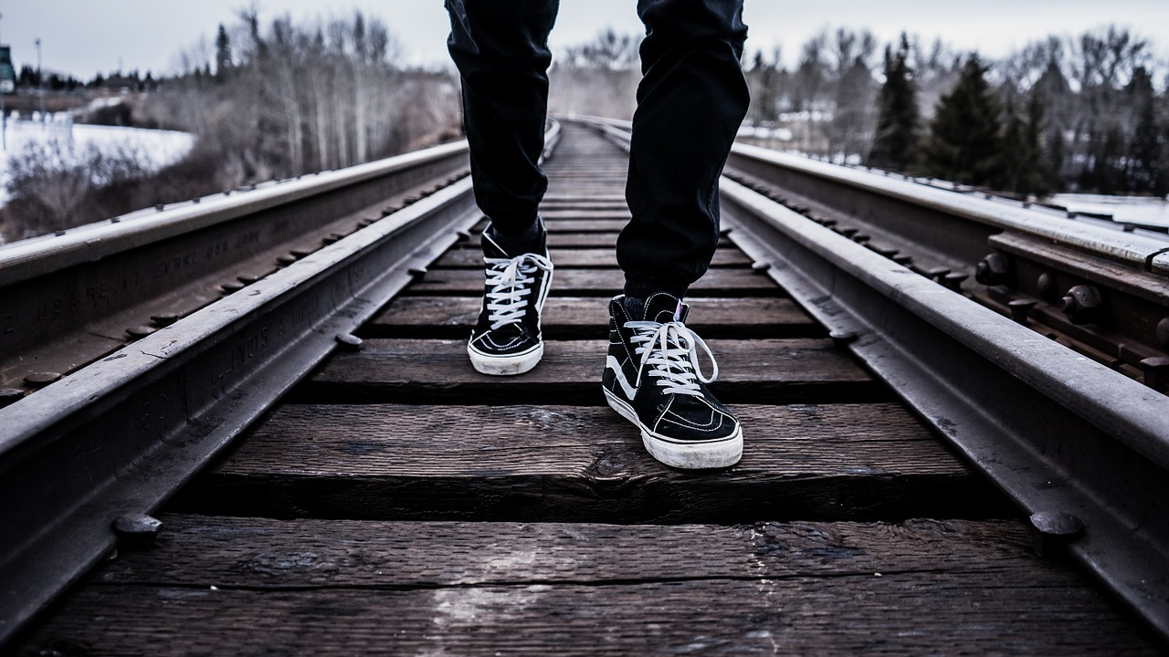 Focus on a man's shoes as he walks down railroad tracks