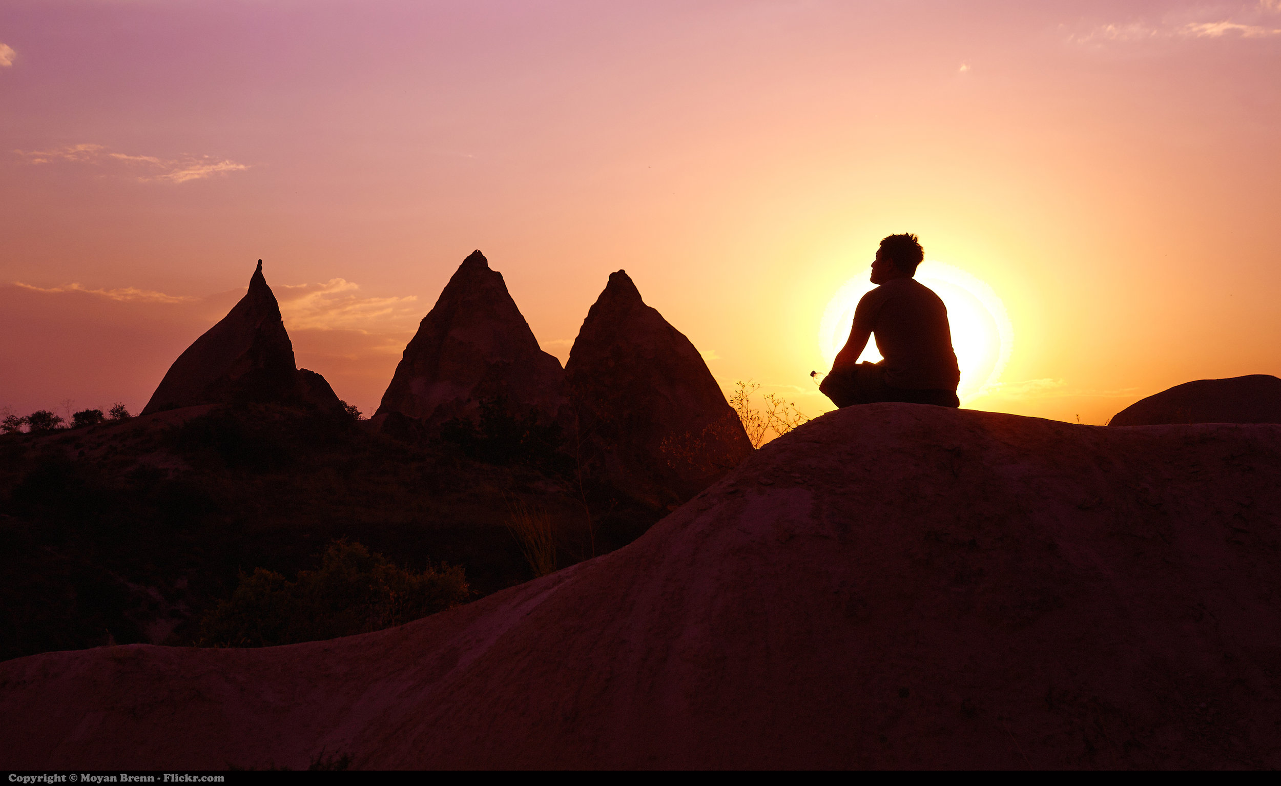 Man sits on red rocks and meditates