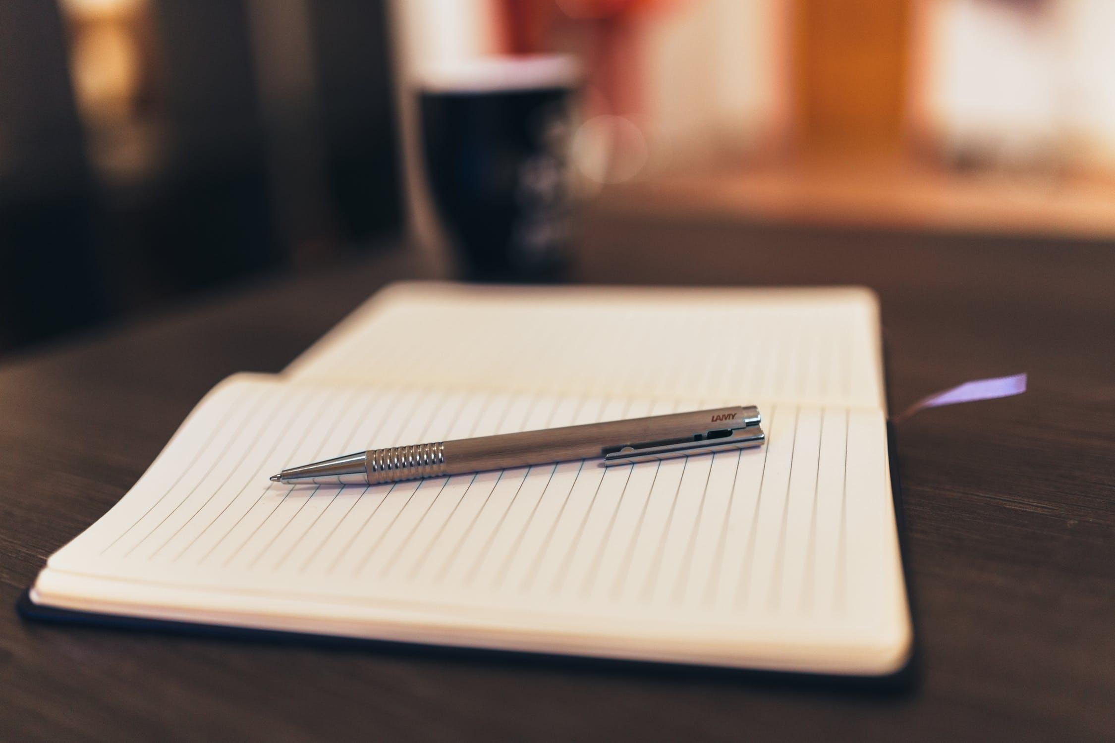 Pen resting on open, blank notebook.