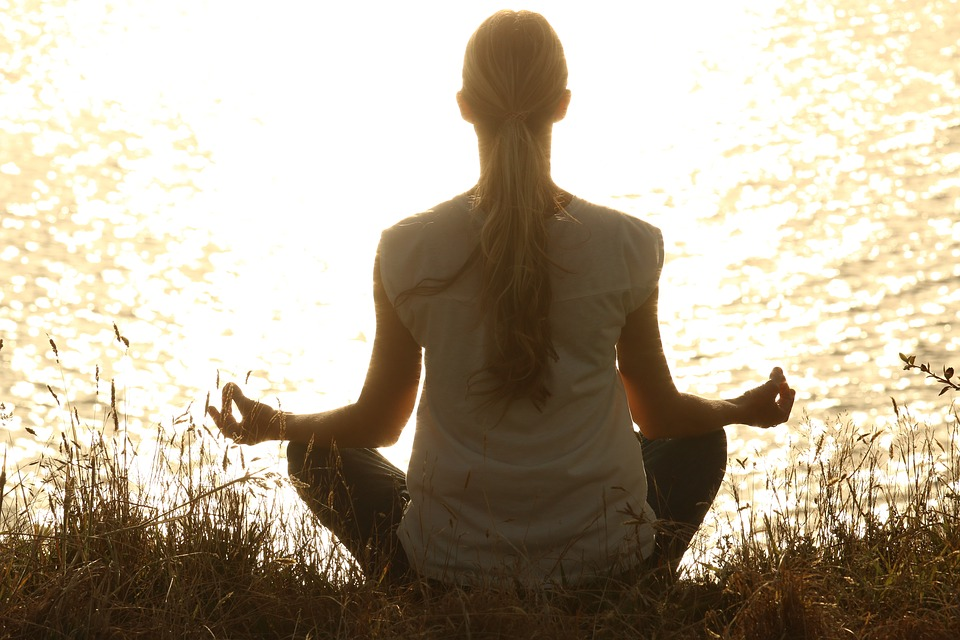 Woman Sits and Practices Meditation Methods at Lakeside During Sunset