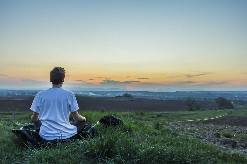 Man Sits and Practices Meditation Methods While Looking Out On Grassy Valley Below