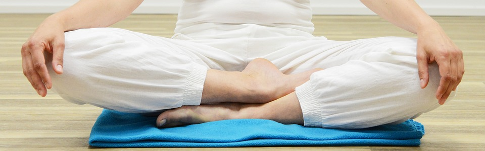 Man in White Sits Cross-Legged on Mat While Meditating