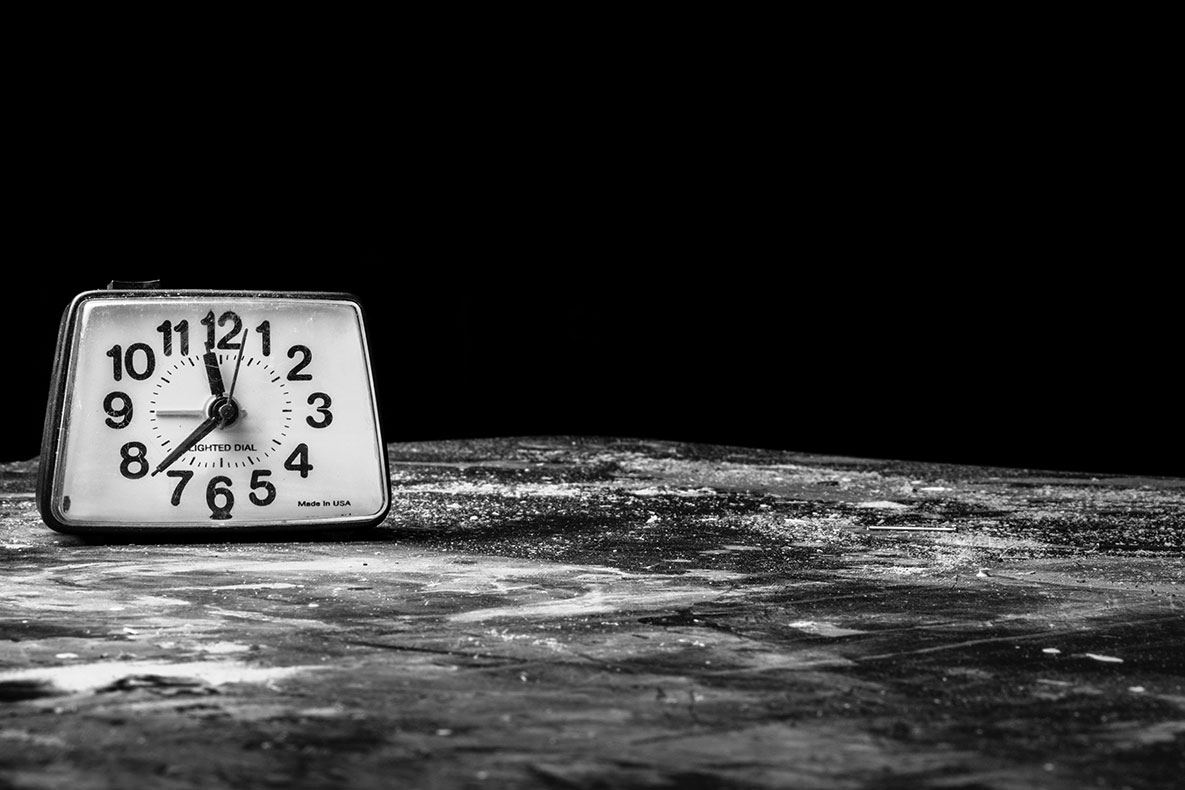 Black and white photo of analog clock on stone surface
