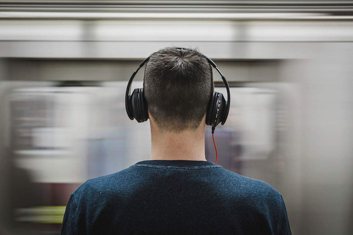 Man wears headphones while waiting for subway train