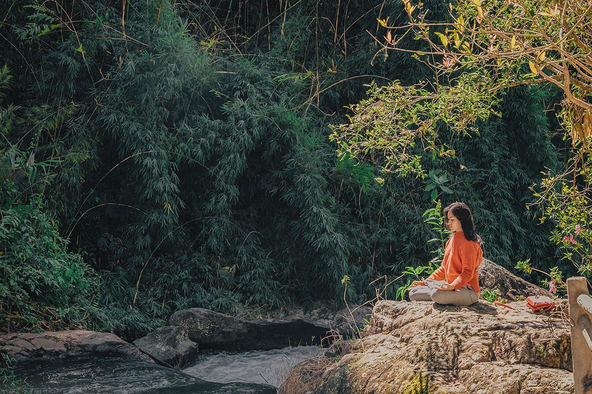 Woman meditates in quiet, open spot near creek