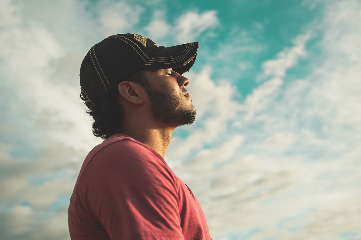 Man practices mindfulness while lifting head to bright blue sky