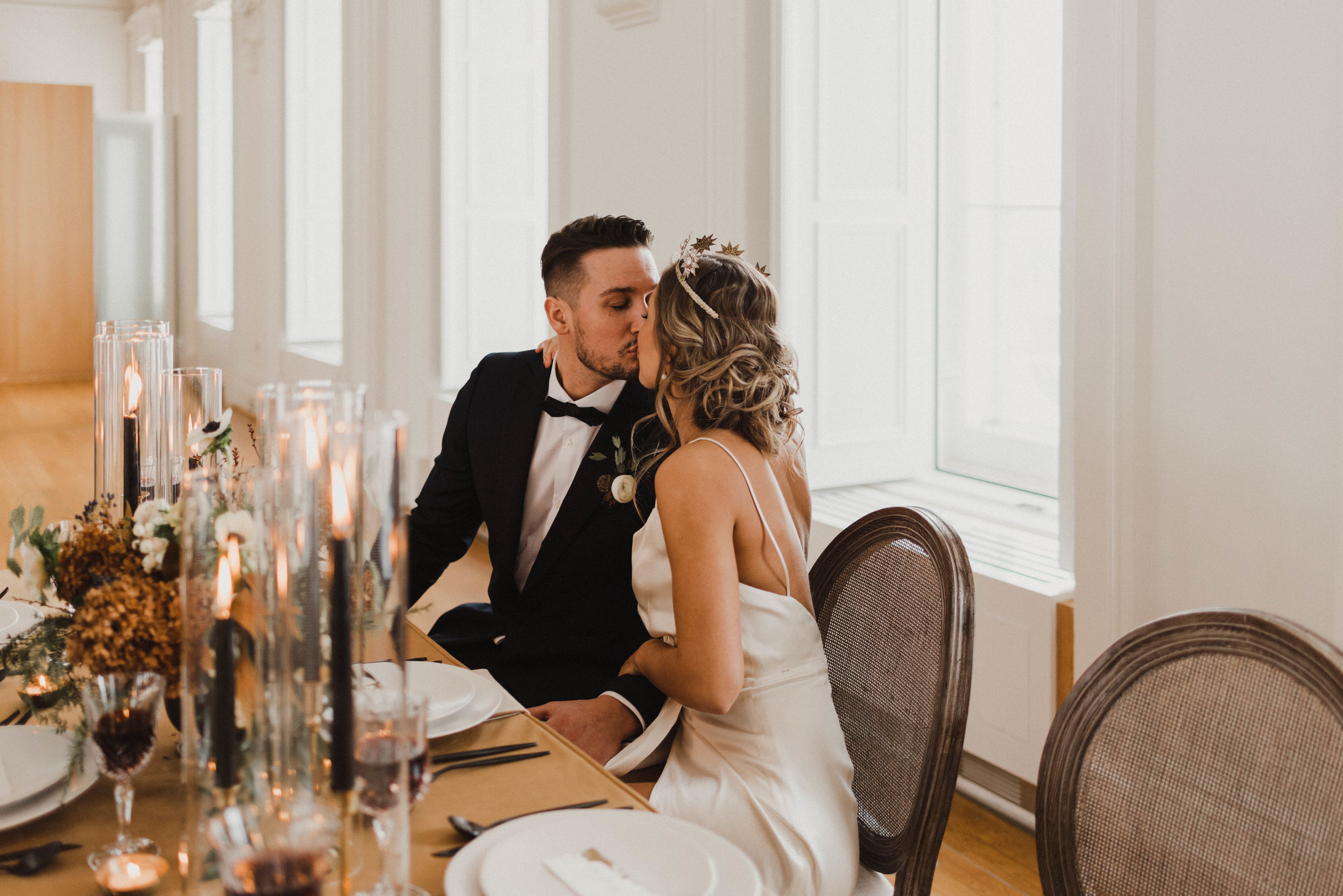 Bride and groom share a kiss at headtable