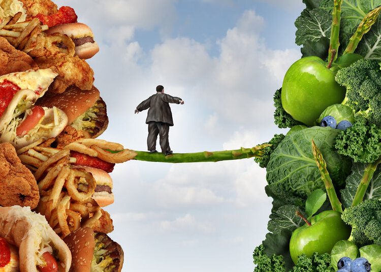 40324179 - diet change healthy lifestyle concept and having the courage to accept the challenge of losing weight and fighting obesity and diabetes as an overweight person walking on a highwire asparagus from fatty food towards vegetables and fruit.
