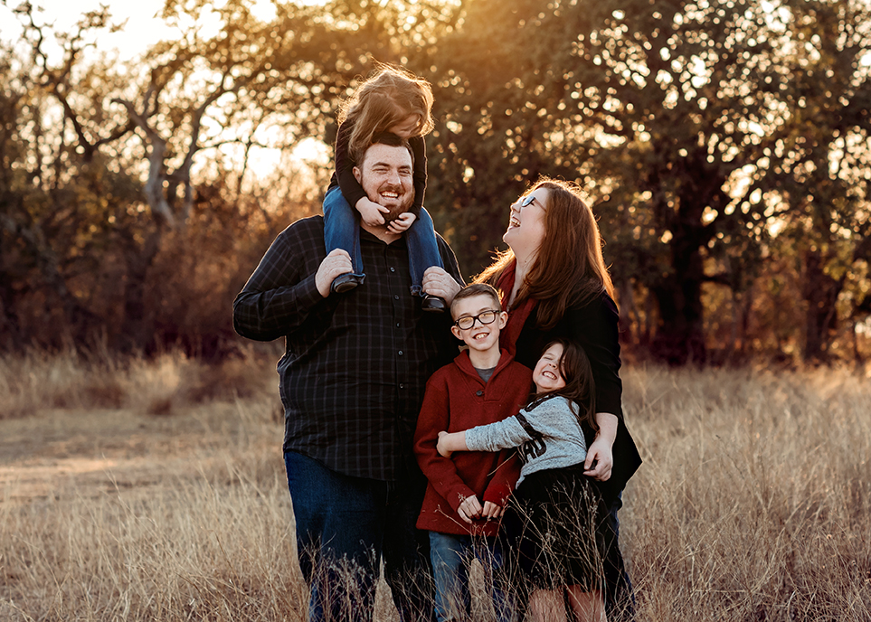 Fort Worth Photographer captures Mom dad and kids laugh between each other at sunset in a beautiful field at Eagle Mountain Park Fort Worth Texas
