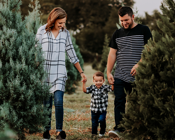 Fort Worth photographer captures mom, dad, and son walking through field of christmas trees!