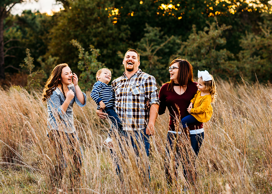 Fort Worth Photographer Jeennie Elissa captures a Family laugh together in the tall fall grass at the Lyndon B National Grasslands in Decatur Texas