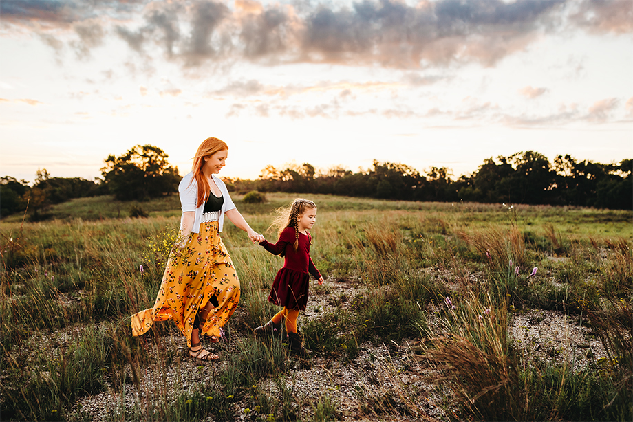 A girl and her mom take a walk at sunrise during a family photography session in Fort Worth Texas