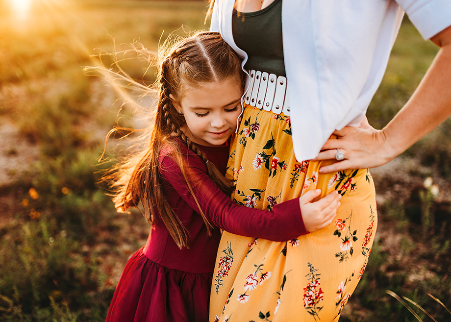 Girl hugs her mom while Fort Worth photographer Jeennie Elissa captures a close up moment of their embrace with the sun rising over the trees shining on them.