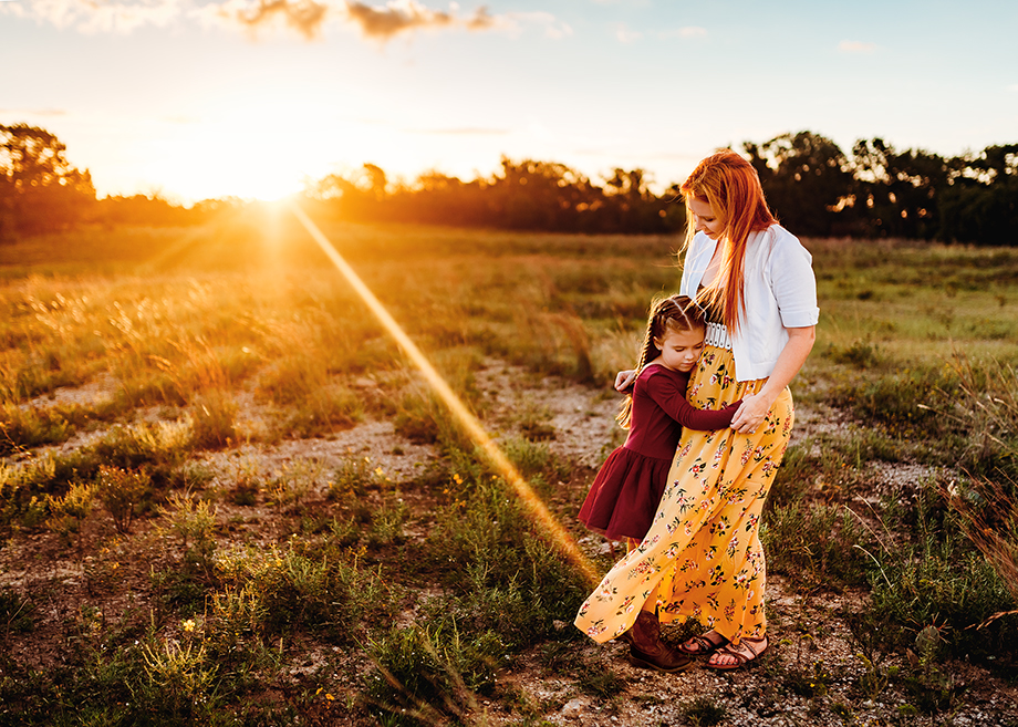 Family photographer sevicing Fort Worth , Weatherford, Burleson, and Decatur Texas. snaps a shot of mom and daughter embracing in a hug at sunrise at LBJ grasslands in Decatur Texas.