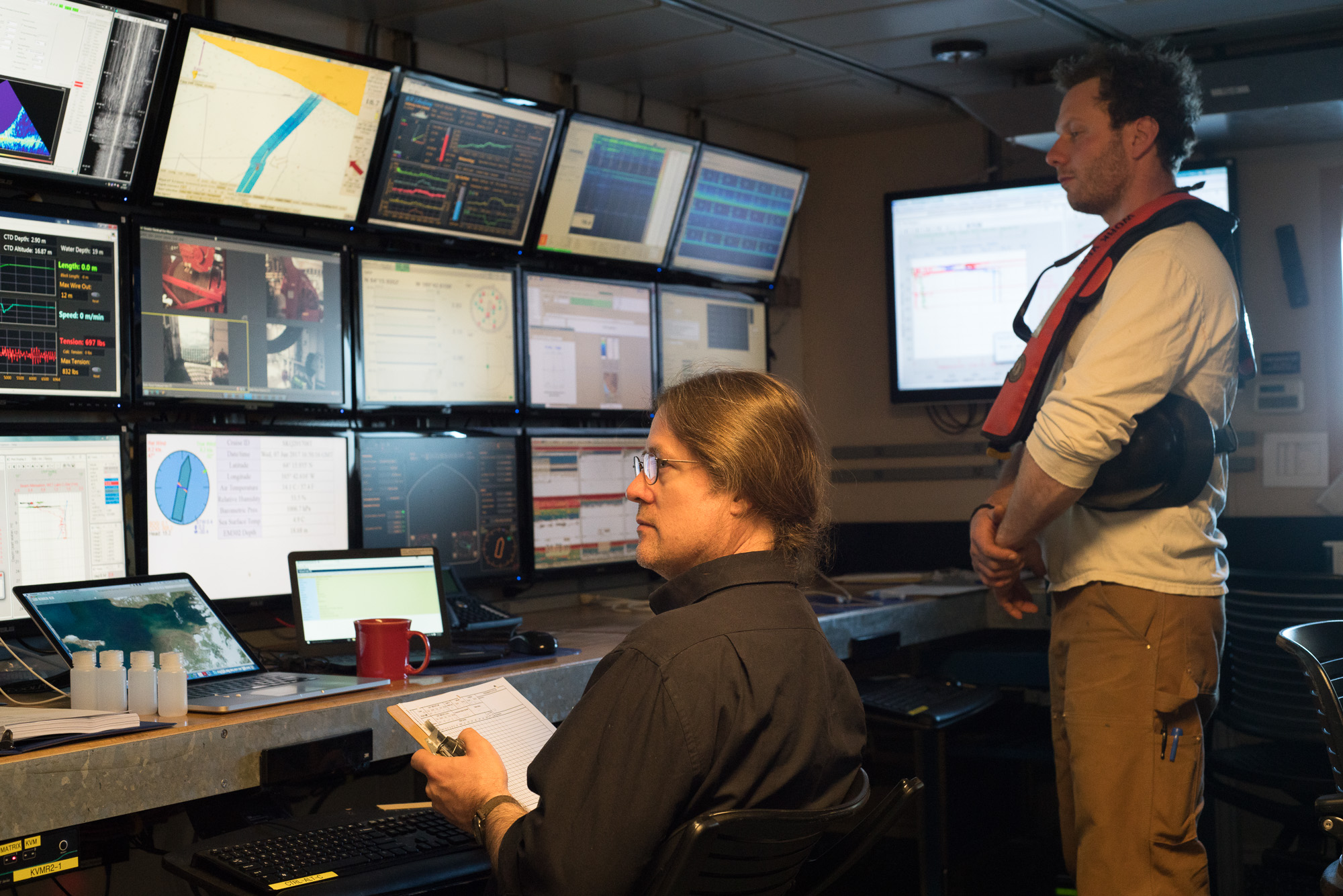 Chief Scientist Seth operates the CTD rosette from the computer lab while Ethan, one of R/V  Sikuliaq 's marine technicians, oversees its operation.