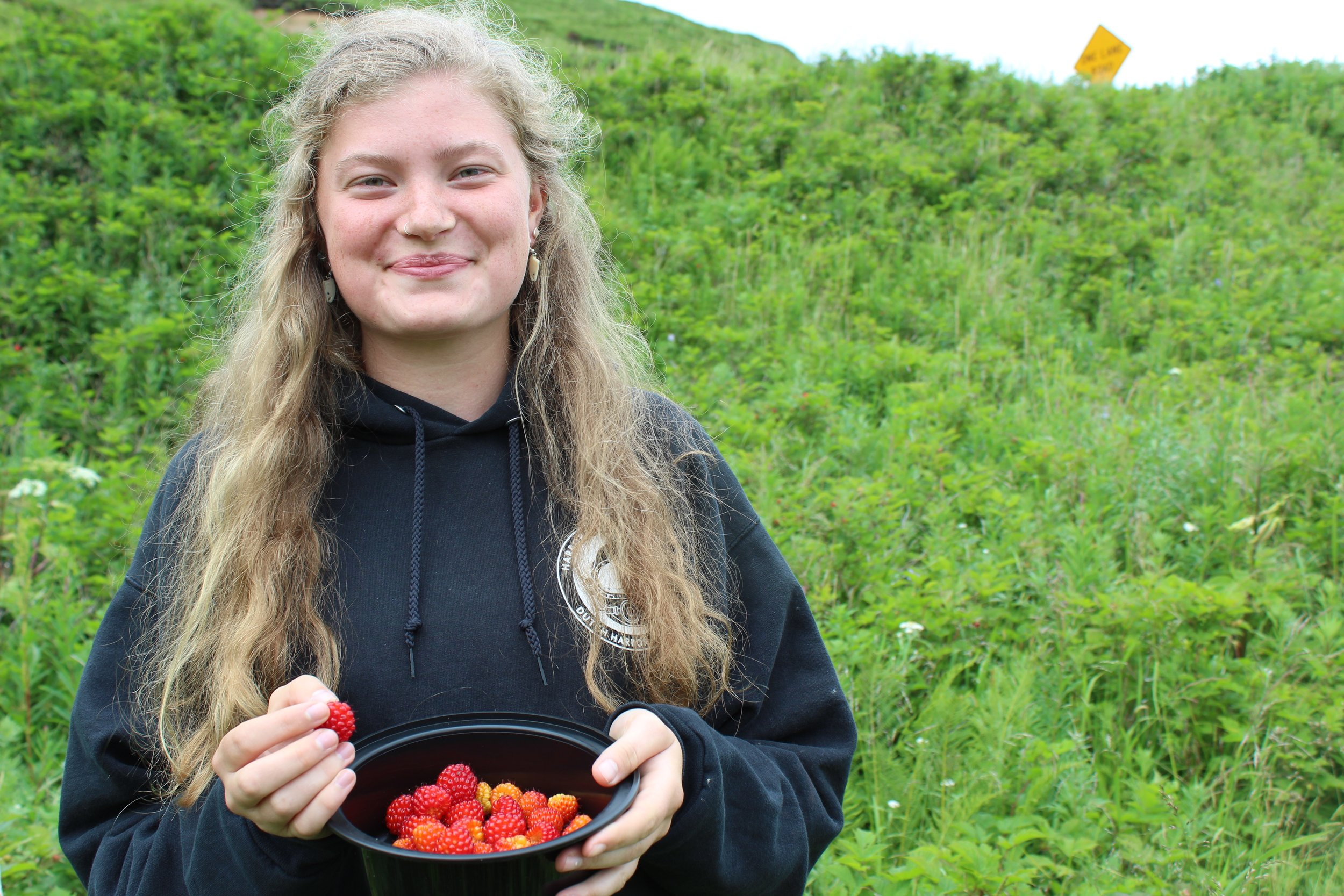 Harmony Wayner enjoying her last bit of time on land before departure, picking salmonberries on Mt. Ballyhoo in Dutch Harbor.