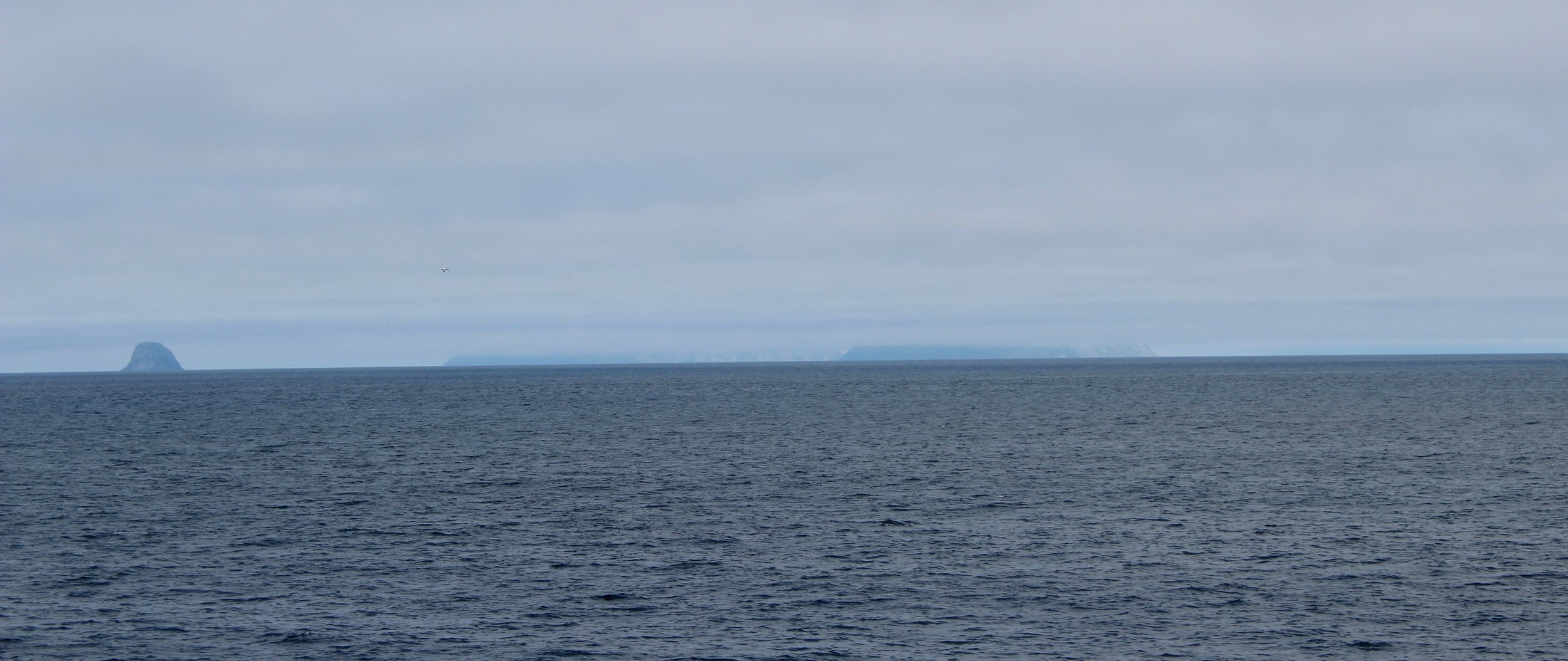 Little Diomede Island and Russia in the distance as seen while passing through the Bering Strait. Photo credit: Harmony Wayner