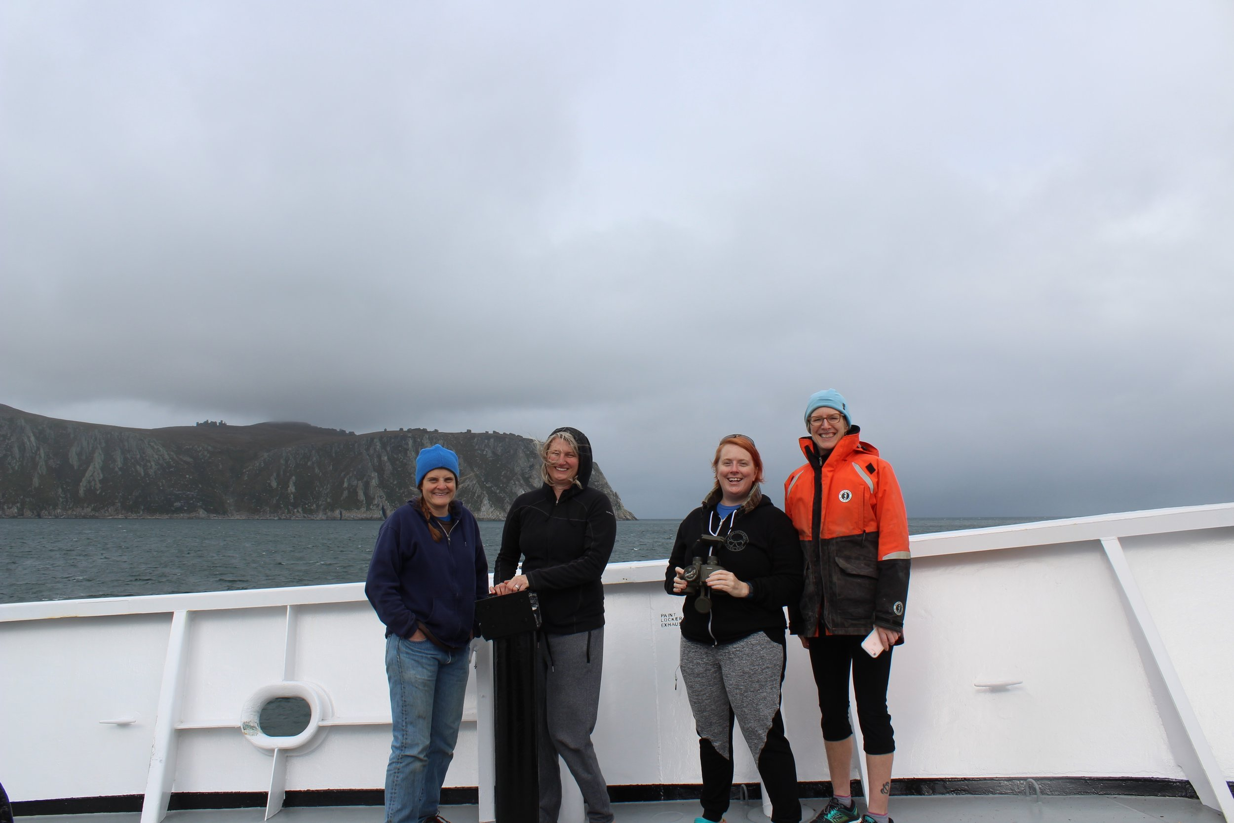 Left to Right:Catherine Berchok, Cathleen Vestfals, Nissa Ferm, and Libby Logerwell, out on bow in front of King Island in the northern Bering Sea. Photo credit: Harmony Wayner