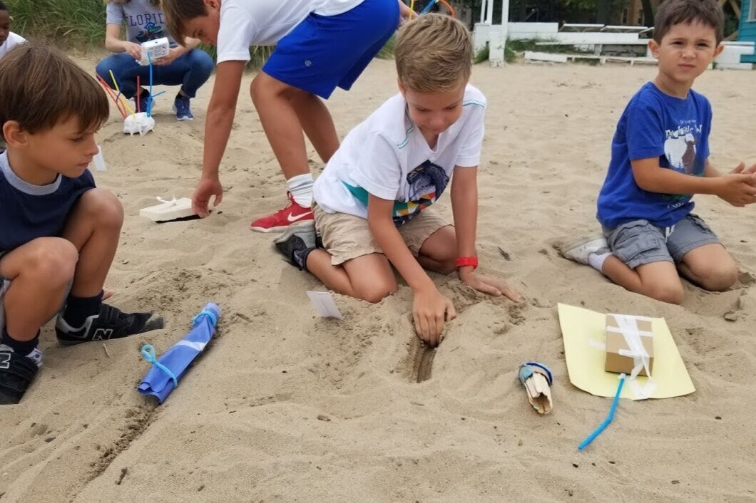 Redwood Day students testing the sand's natural temperature.