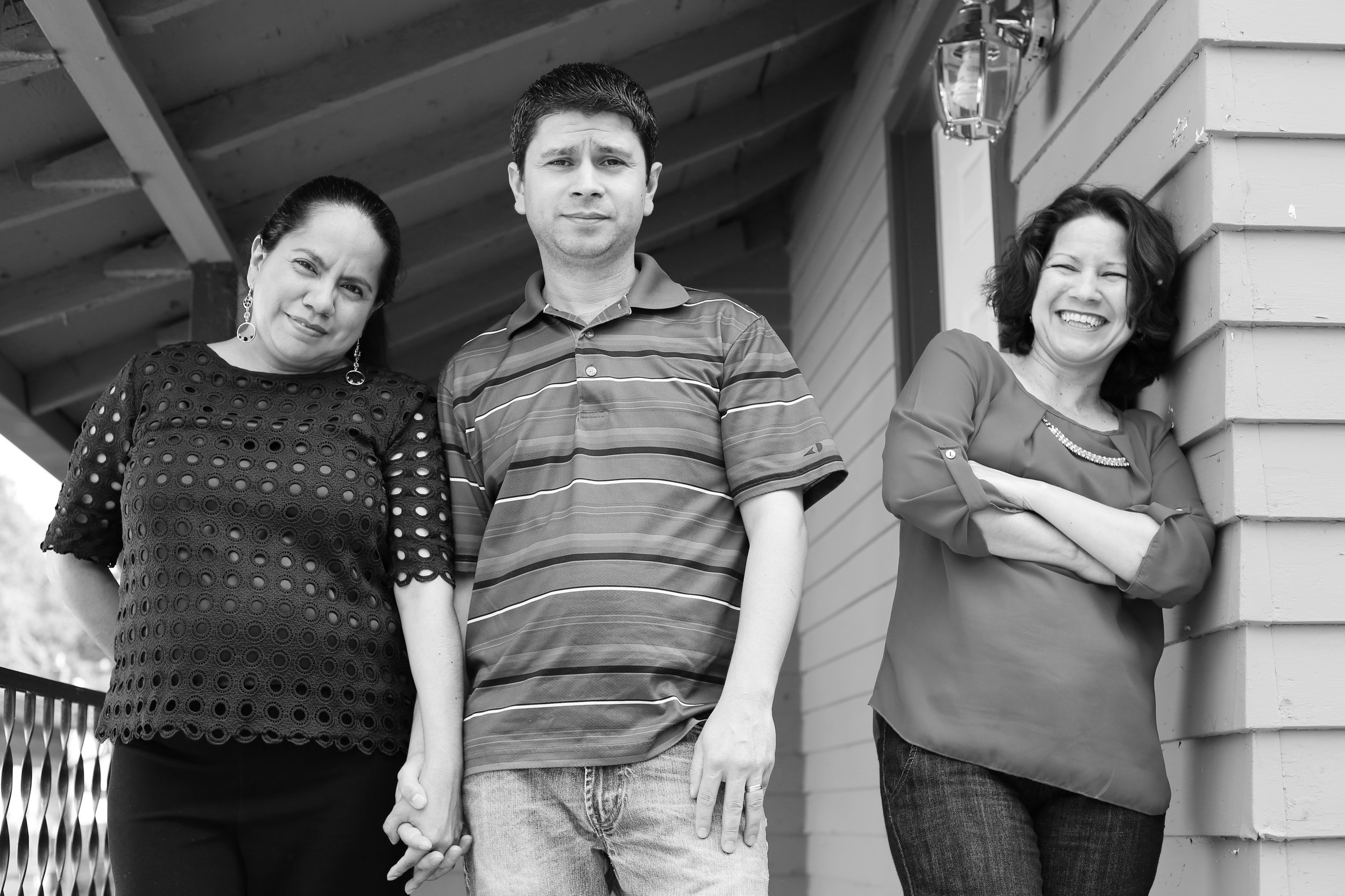 Olga, her husband, and sister-in-law, in front in front of the house they were able to purchase.