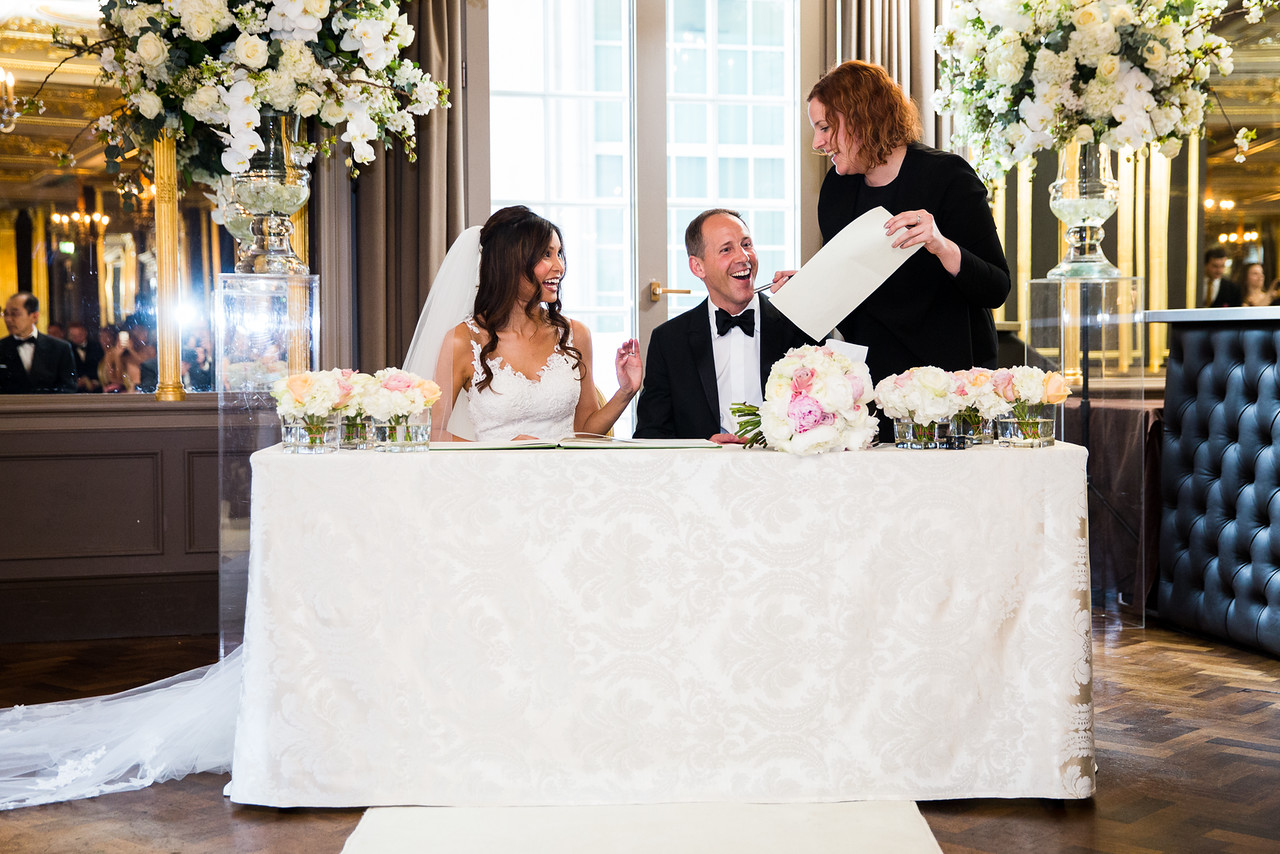 Bride and Groom Laughing While Signing of The Register London Wedding