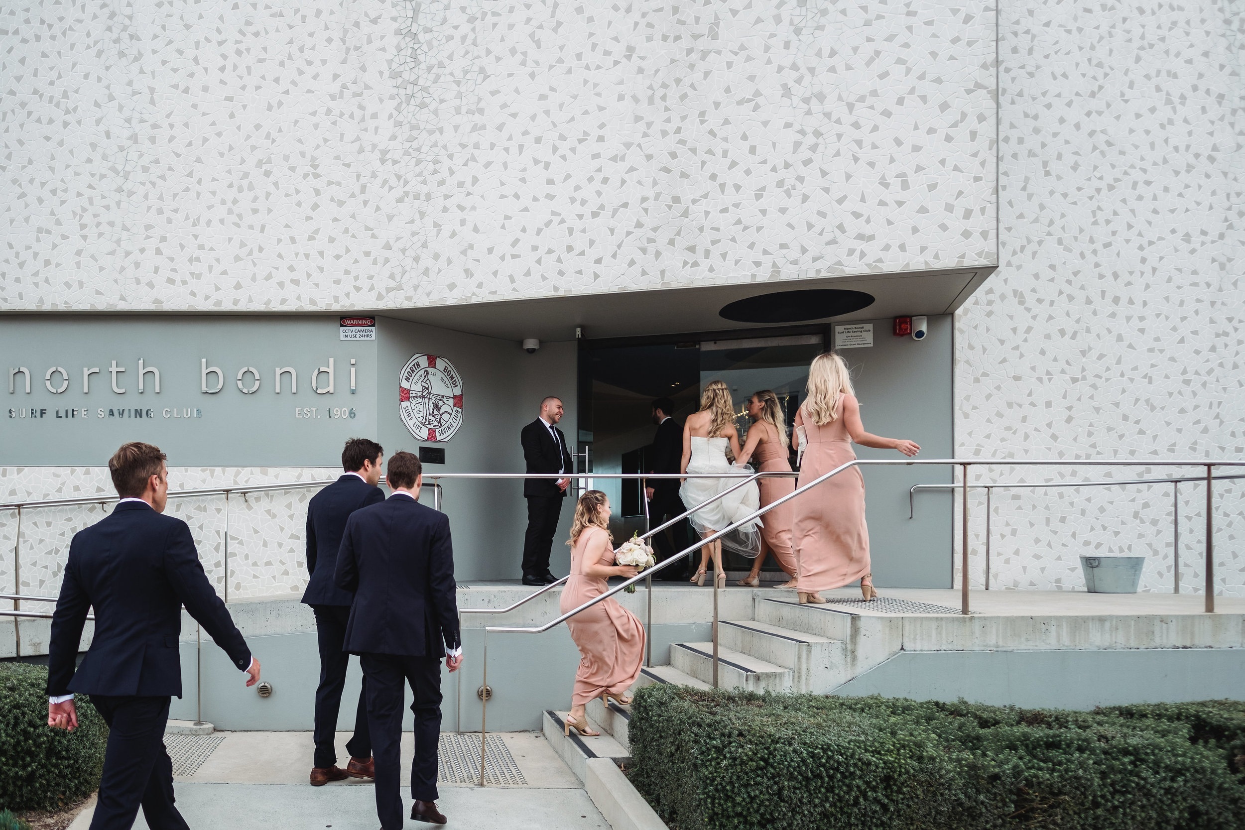 Bridal party going into North Bondi Surf Club for wedding reception