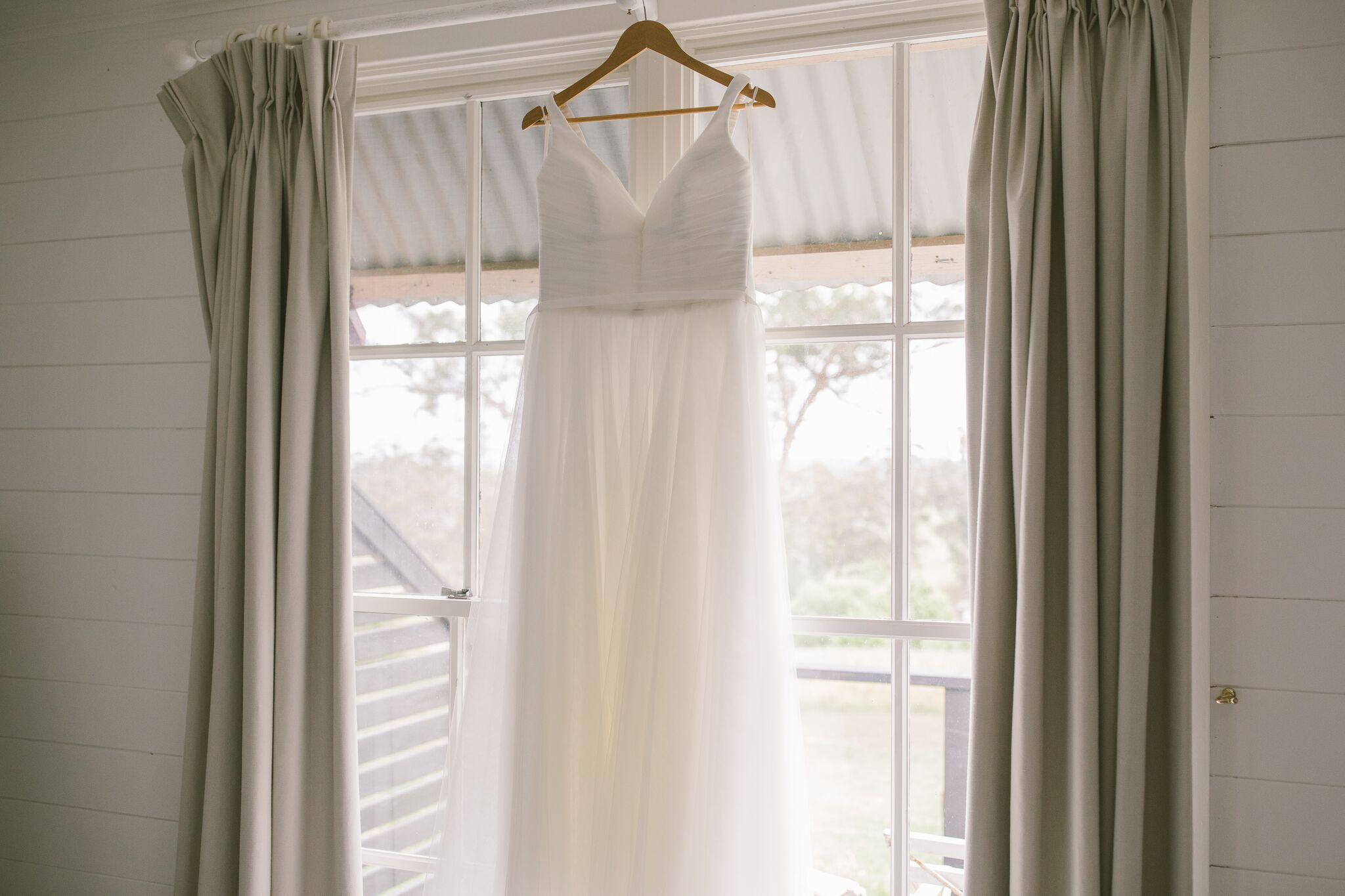 Wedding dress hung up on a window in Mali Brae Farm Wedding