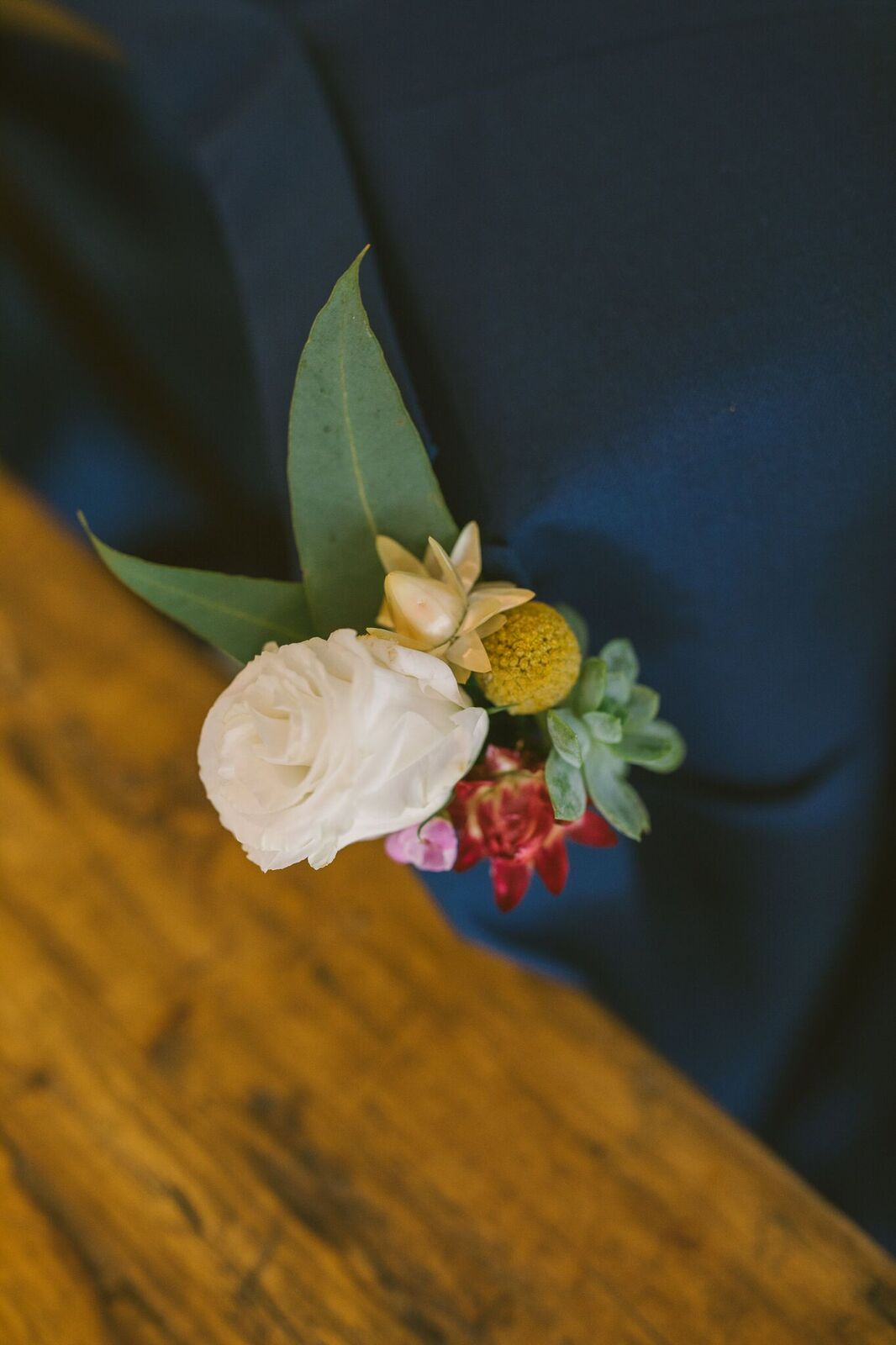 Grooms button hole with white flowers and native wedding flowers