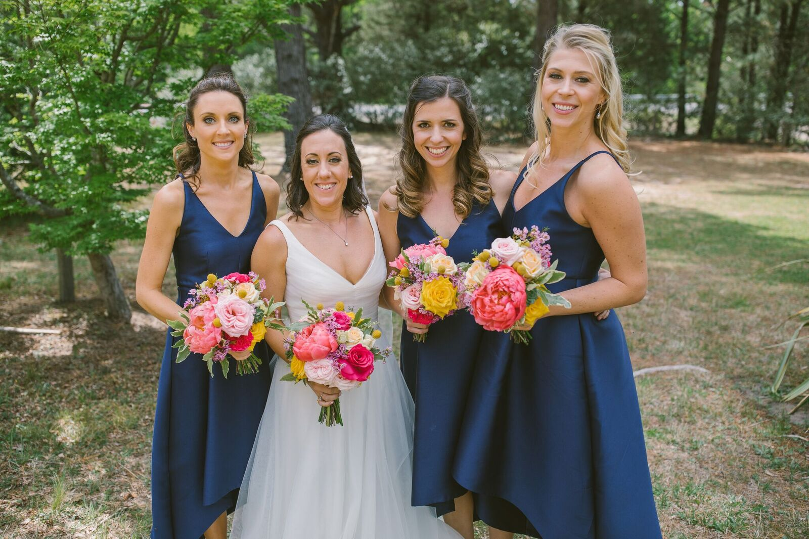 Bride and Bridesmaids holding bright pink and yellow flowers