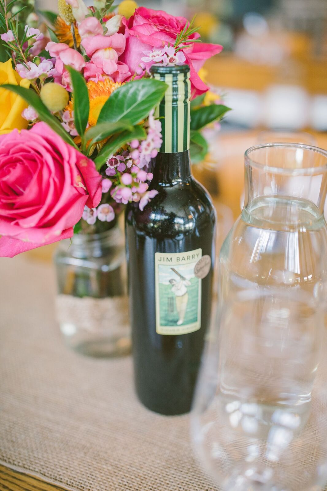 Bottle of wine with pink, purple and yellow wedding flowers