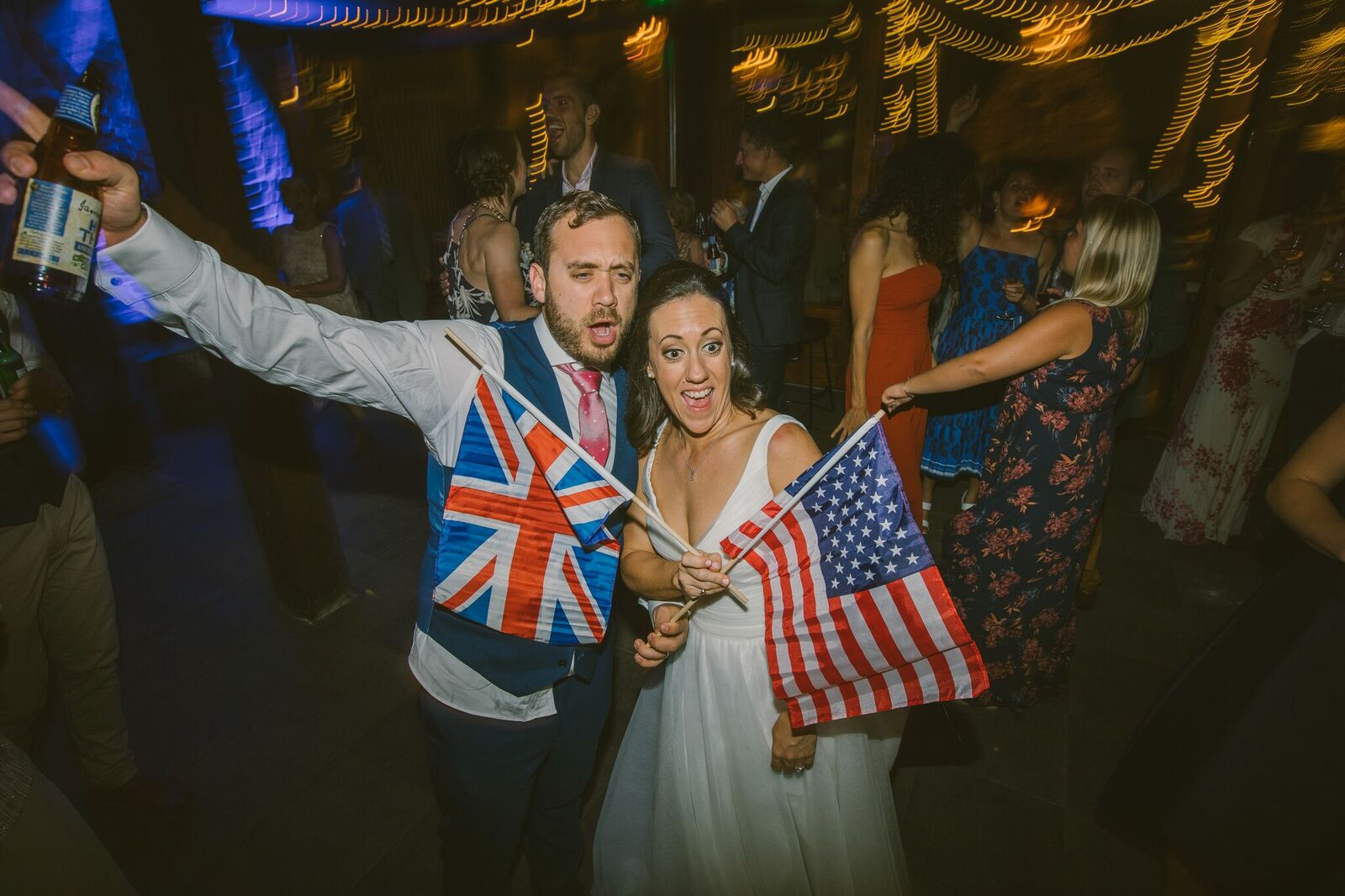 Bride and Groom holding an American and English Flag each