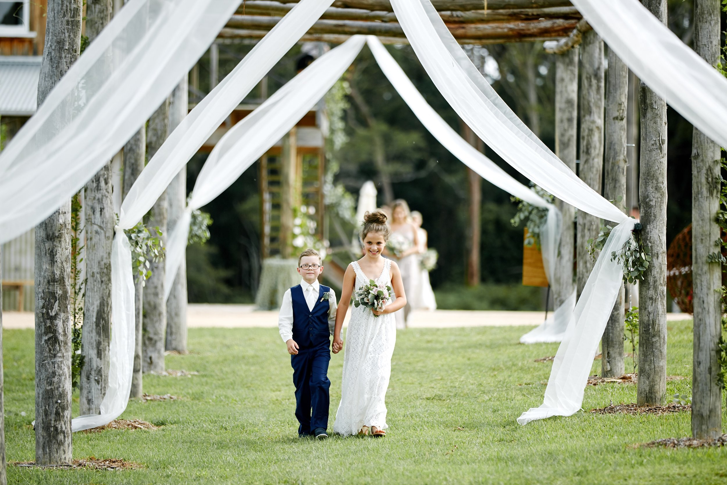 Flower girl and page boy walking down the aisle at an outdoor wedding in NSW Central Coast Wedding venue The Stables of Somersby