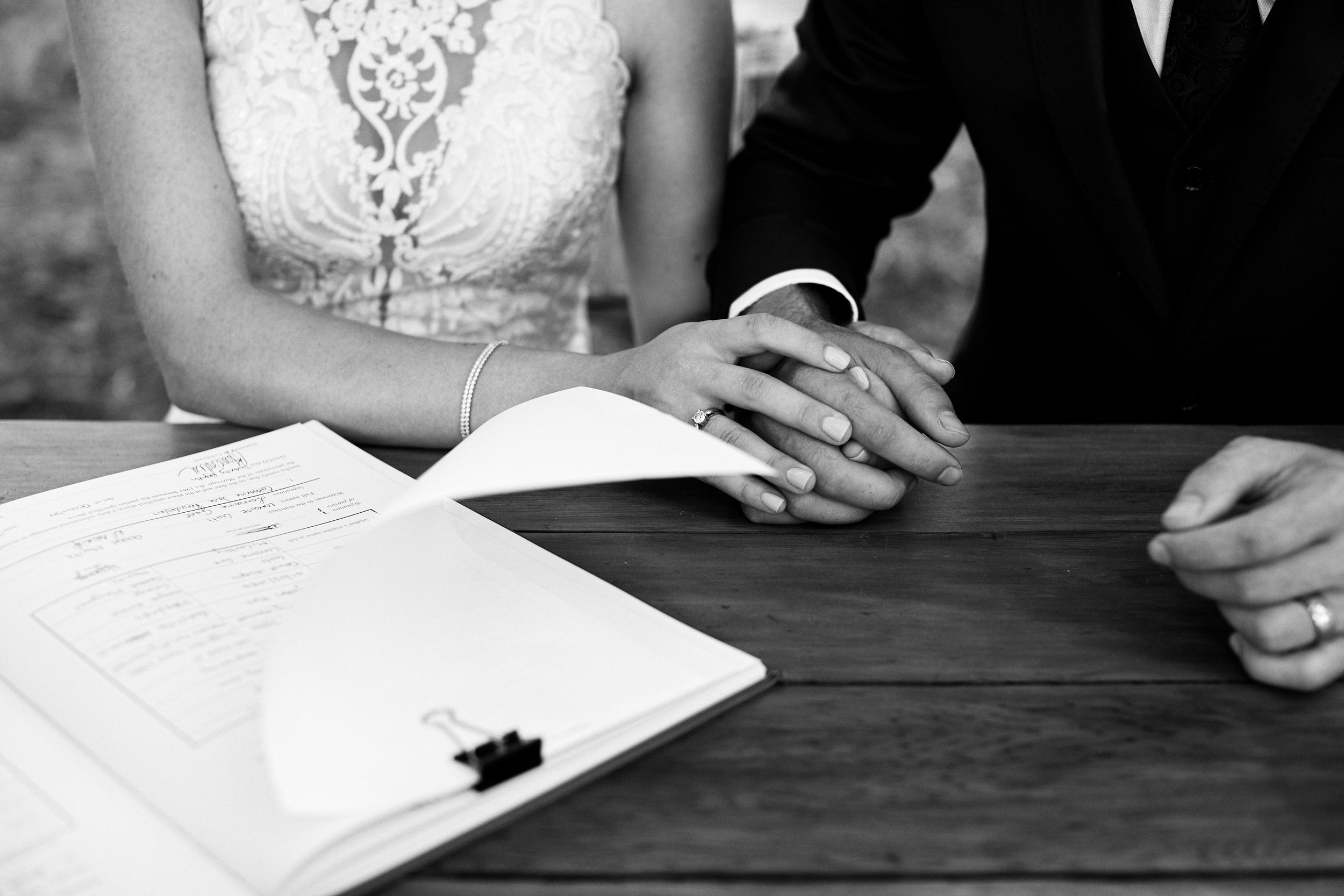 Bride and Groom holding hands as they sign the register