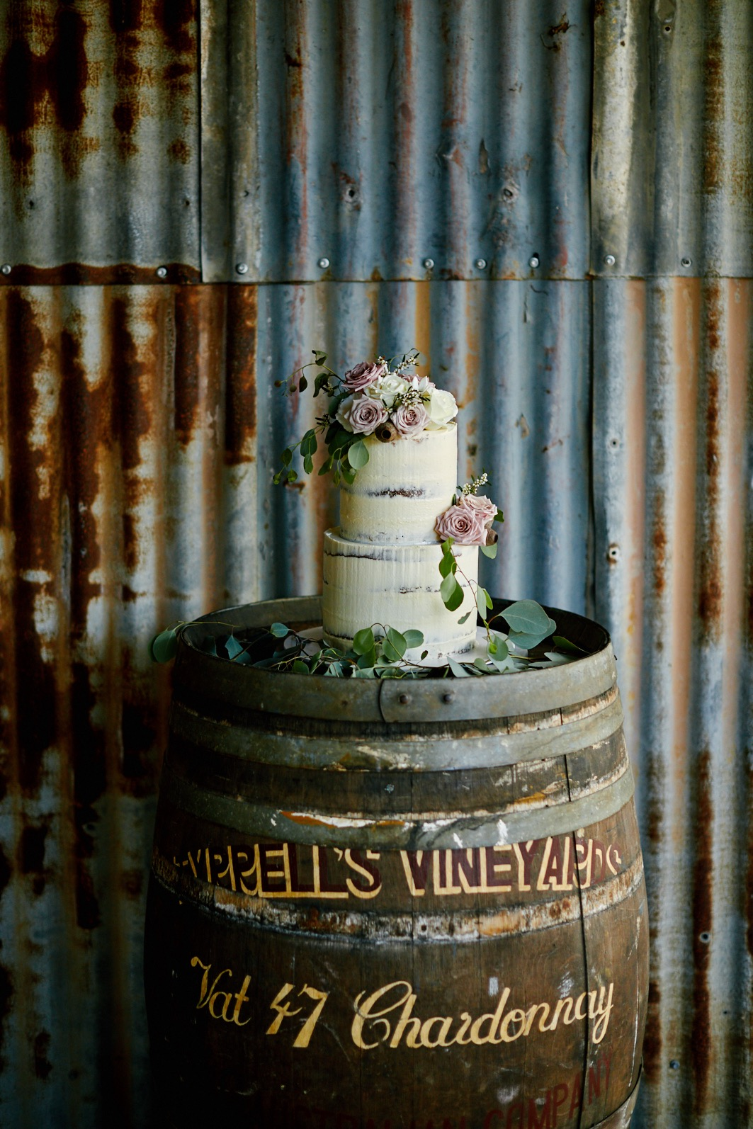 Two tier semi naked cake with pink flowers displayed on a barrel at The Stables of Somersby barn rustic wedding venue in NSW Central Coast