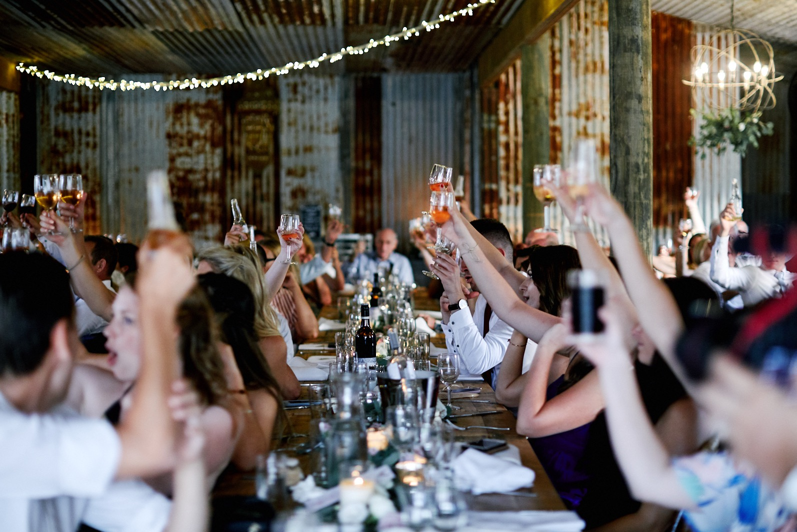 Guests toasting their drinks at The Stables of Somersby barn wedding venue. Rustic wedding venue.