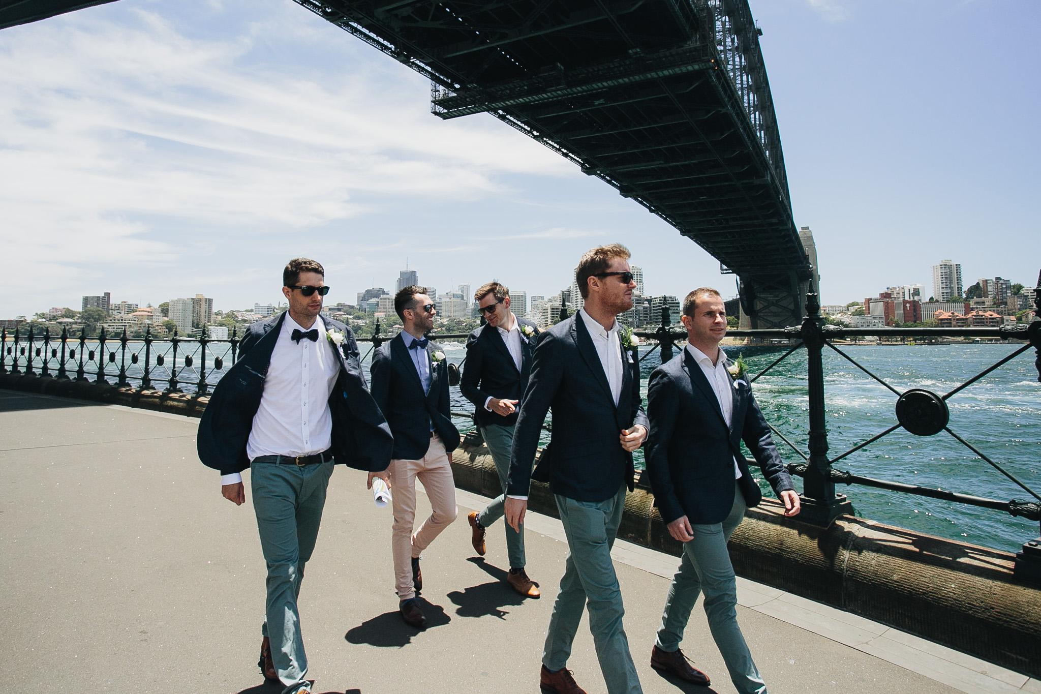 Groom and Groomsmen walking along Sydney Harbour under the Sydney harbour bridge on the wedding day