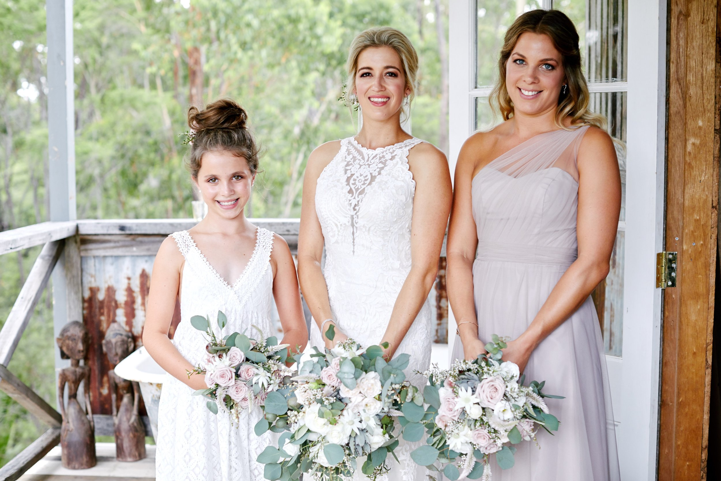 Beautiful bride before her wedding looking over one shoulder with her veil and bridal pink and white bouquet of flowers. Central Coast NSW wedding venue.