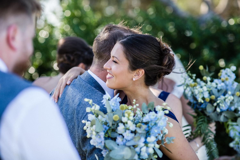 BRIDESMAID HUGGING GROOM AT BONDI BEACH WEDDING PLANNED BY WEDDING PLANNER SAMANTHA BURKE