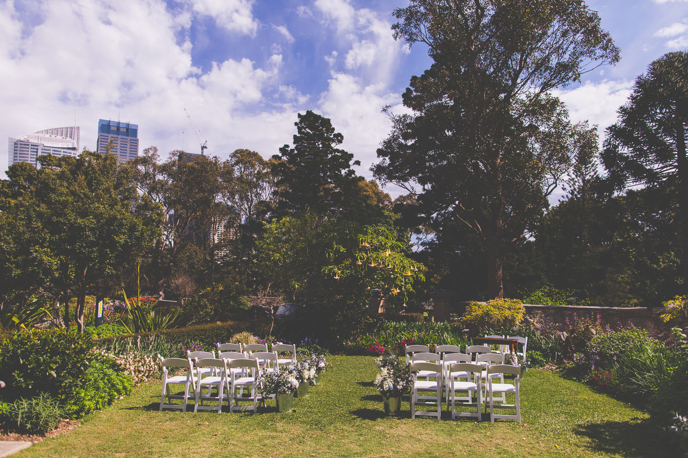 Wedding at Lion Gate Lodge with white chairs and buckets of flowers