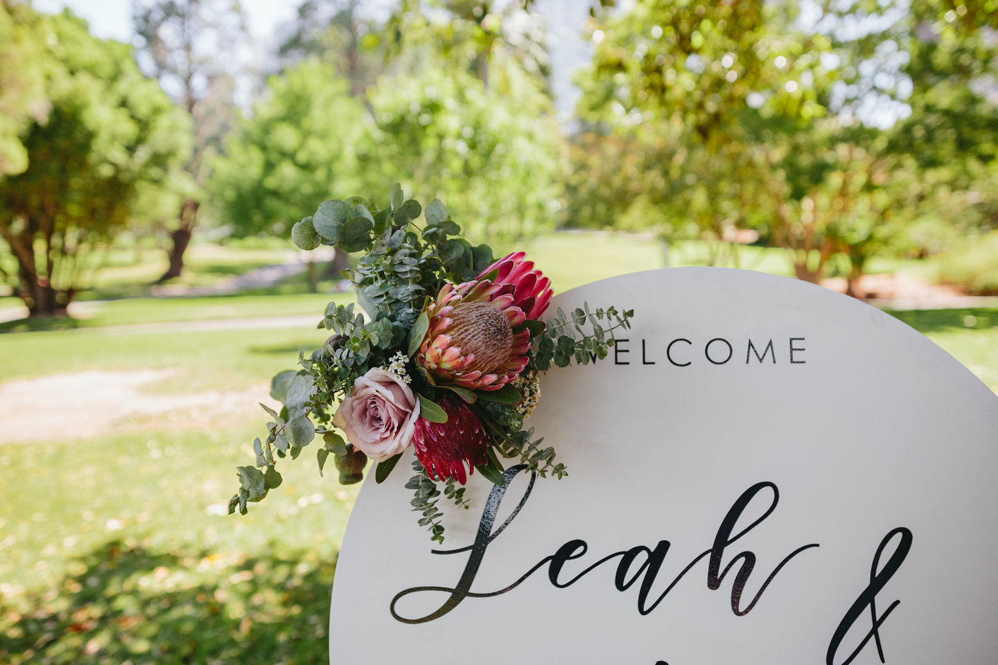 Round wedding welcome sign with Australian native flowers. Protea and roses displayed at The Fig Tree Lawn Royal Botanic Garden Sydney wedding