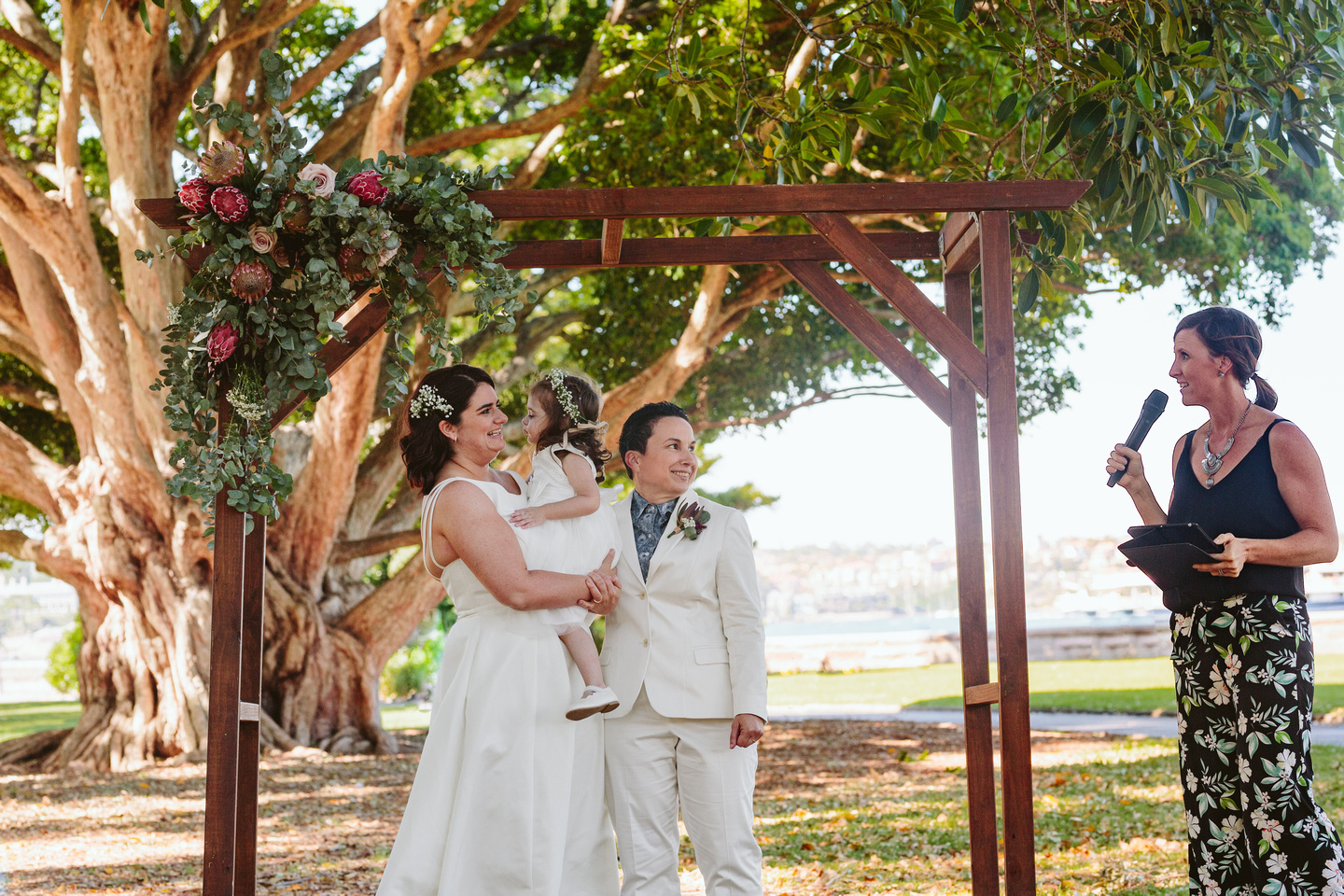 Couple on their wedding day with their daughter at The FIg Tree lawn Royal Botanic Garden Sydney