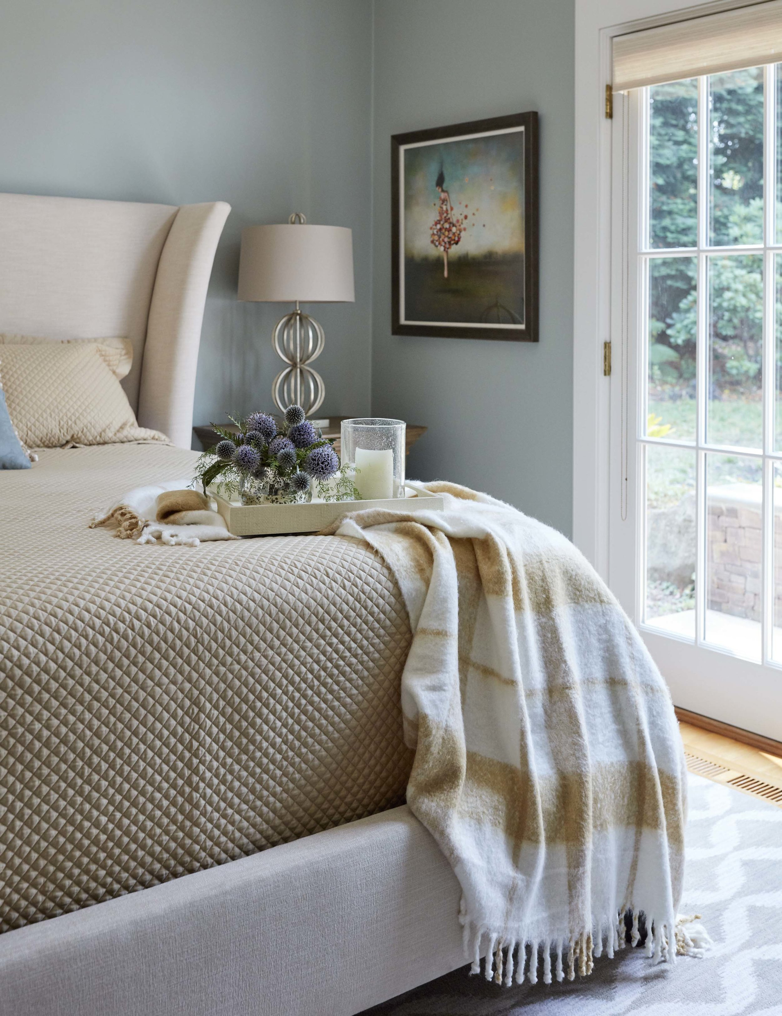 Blueish-green walls set the tone for this serene guest room.