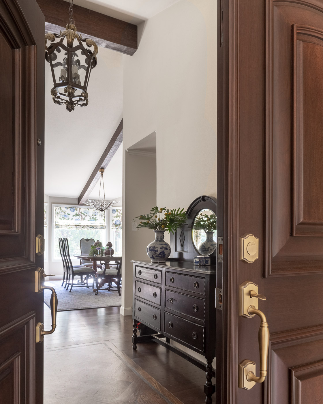 Glimpses of the exquisite Dana Creath iron lantern through chocolate brown entry doors.